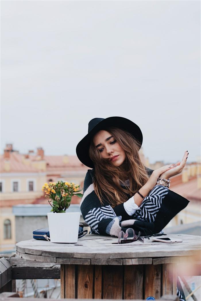 Idée comment s'habiller comme une fille tumblr, belle fille avec grand manteau et chapeau style bohème chic, cheveux longs, photo toit de Lisboa, adopter le style fille Tumblr
