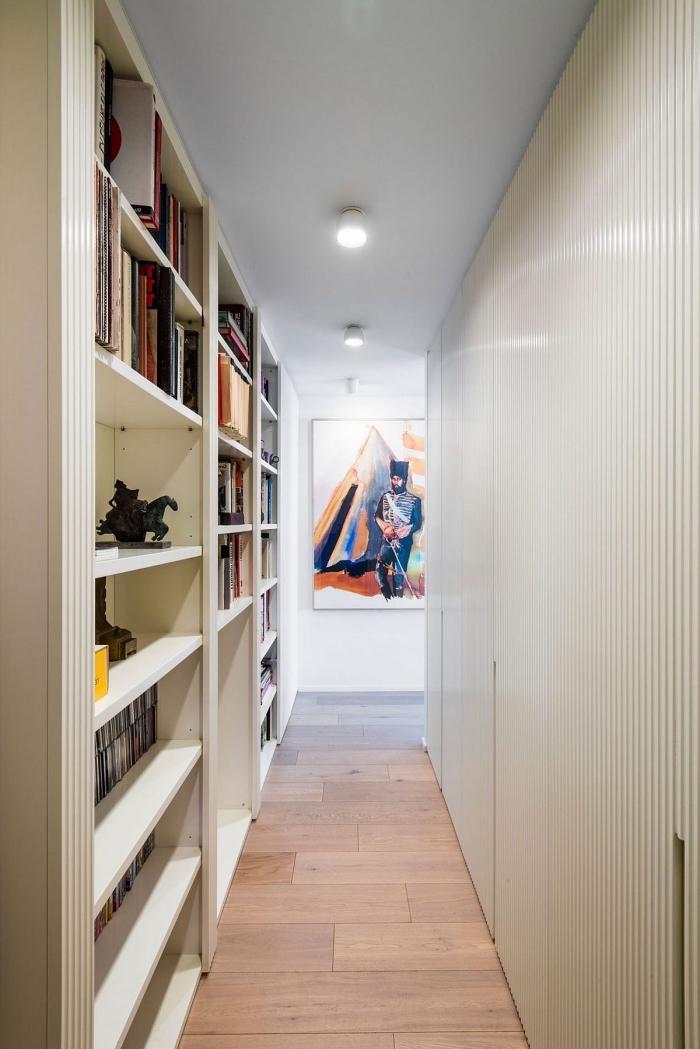 decoration couloir long et étroit avec une bibliothèque aménagée le long du mur, aménagement d'un couloir étroit fonctionnel, couleur de peinture blanche mur du couloir aménagé en bibliothèque
