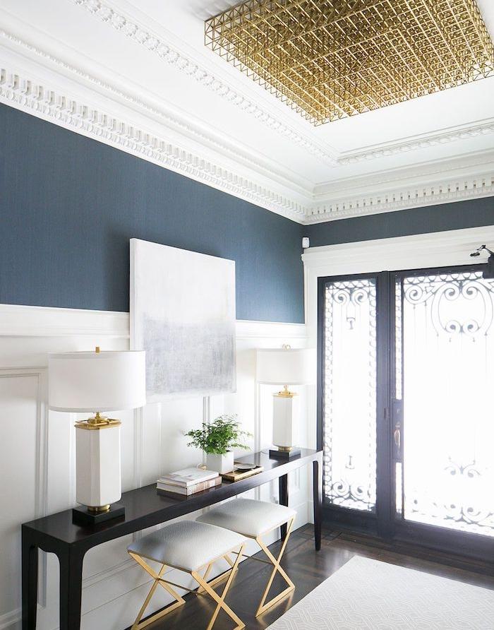 porte d entree ajourée soubassement bois blanc, console noire, tabourets, mur couleur indigo, tapis blanc sur parquet foncé, lustre original