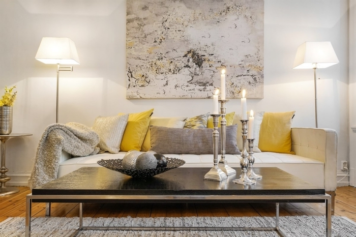 exemple de salon gris et jaune cozy aux murs blancs et parquet bois avec accessoires coussins et bougeoirs en gris