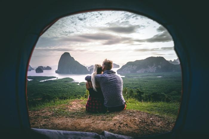 Couple amoureux assise sur la pelouse avec une belle vue de sa tente, image st valentin, carte a envoyer a son amoureux bonne saint valentin