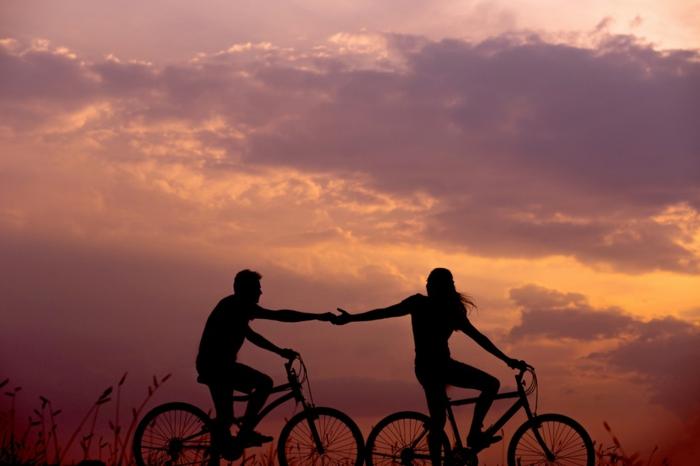 Cool photo de couple silhouettes de homme et femme qui se tiennent par la main au meme temps sur leurs bicyclettes, ciel rose-violet