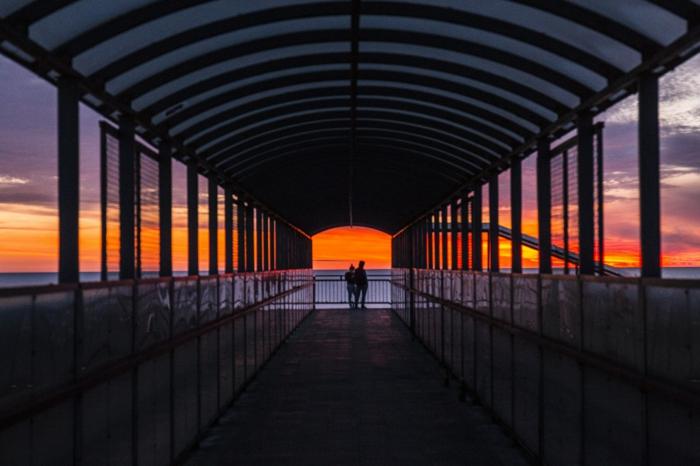 Le bout d'un pont au bord de la mer, pier couple silhouettes au coucher du soleil, image couple amoureux, image romantique parfait photo à utiliser comme fond d'écran romantique