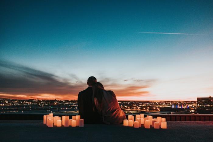 Couple amoureux assise pour saisir la beauté de la vue, bougies allumés autour d'eaux, les lumières de la ville