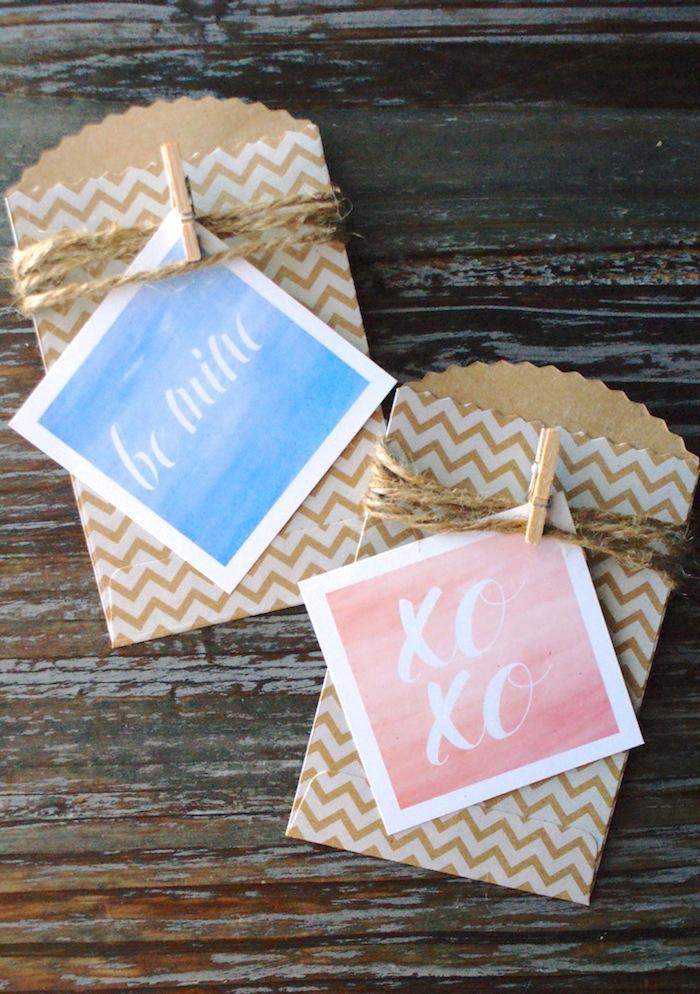 idée de petite carte de voeux avec simple texte en lettres blanches sur fond rose ou bleu à effet aquarelle et enveloppes à effet chevron avec pince à linge bois et ficelle de chanvre