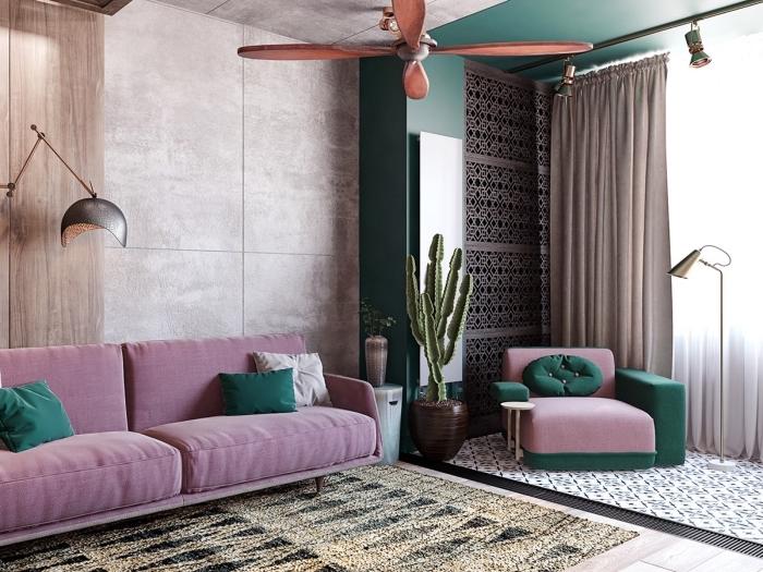 modèle de canapé rose décoré avec coussins de couleur vert pin, revêtement mural en panneau bois, tapis beige et noir aux motifs géométriques