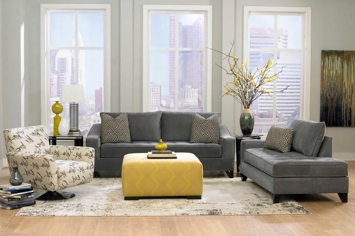 déco de salon gris et jaune avec plancher de bois clair, mobilier salon canapés gris et table ottoman de couleur moutarde