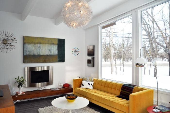 salon cozy aux murs blancs avec poutres plafond apparentes en bois blanc, modèle de canapé moutarde avec coussins