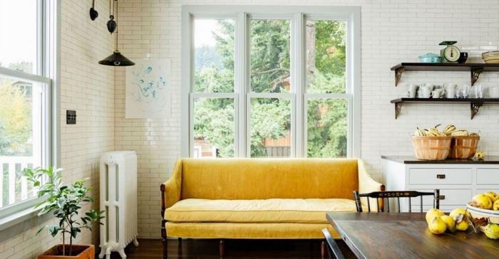 style campagne dans une cuisine blanche aménagée avec meubles bois foncé, modèle de canapé jaune moutarde et bois foncé