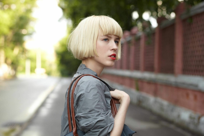 coiffure carré blond mi long, chemise grise, sac à épaules, frange droite, coiffure tendance femme
