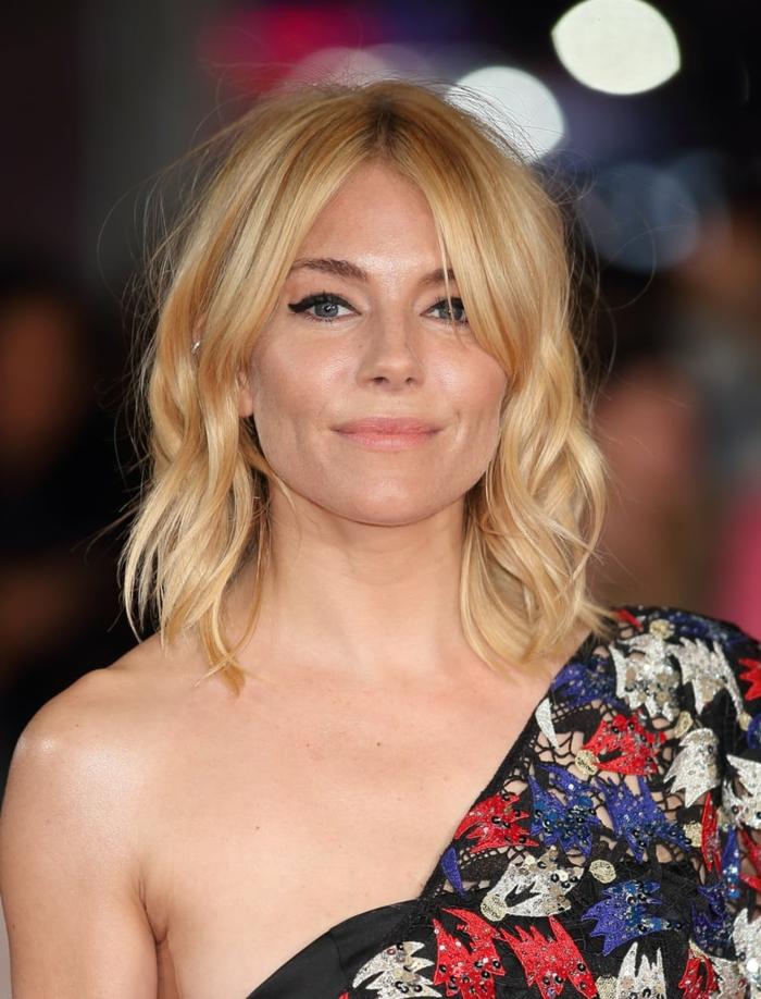 carré long blond avec frange rideau, chemise florale épaules asymétriques, jeune femme aux cheveux ondulants