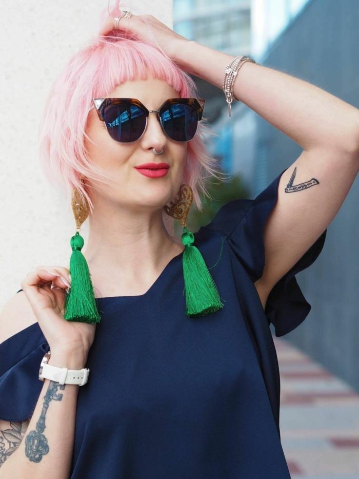 cheveux couleur rose pâle, coupe carré court, boucles d'oreilles franges vertes, lunettes e soleil rondes, frange hachée
