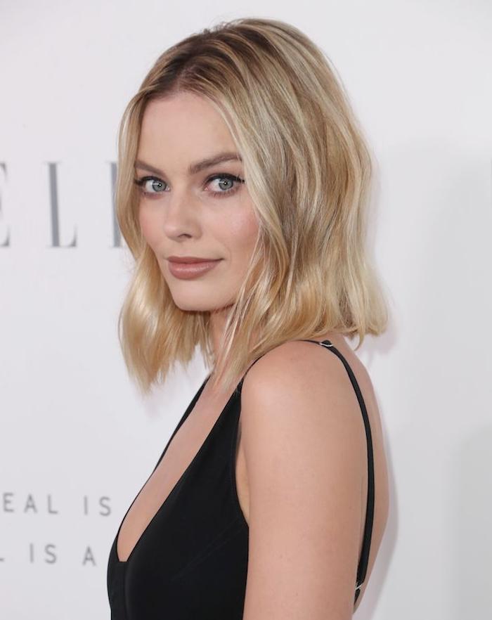 margot robbie avec un carré plongeant long sur cheveux blond clair et racines foncées, robe noire à bretelles
