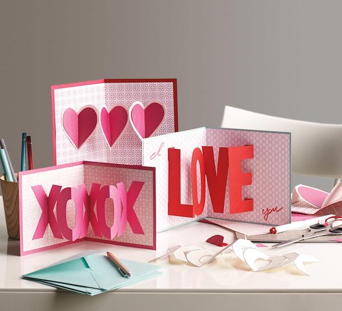 carte pop up 3 d en papier, motif xo, le mot amour et coeurs couleur rose et rouge sur fond rose, enveloppes bleues