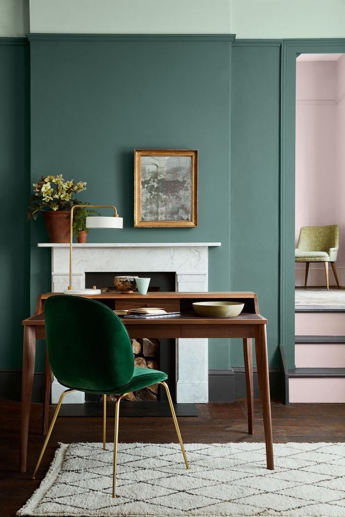 salon aux murs design bicolore de nuances vertes, modèle de bureau bois foncé avec chaise velours vert foncé aux pieds dorés