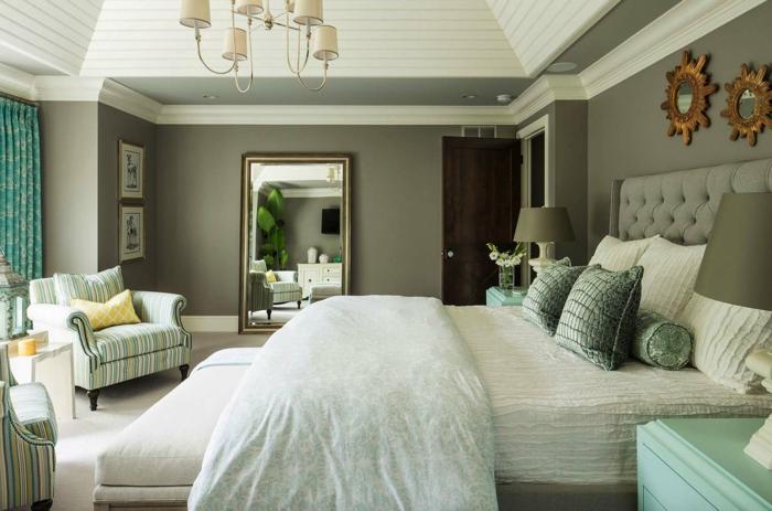 peinture vert de gris dans une chambre, féminine, miroirs décoratifs, plafonnier baroque, fauteuil bleu, mur gris, coussins déco, plafond lattes de bois