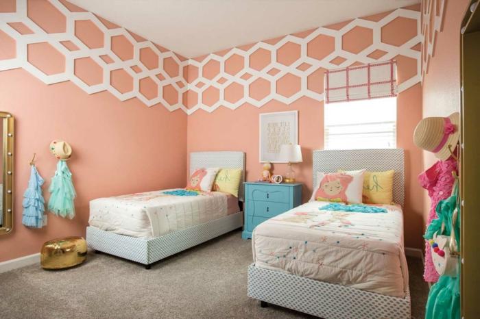 couleur pêche, deux lits, déco en bleu et rose, mur rose, déco géométrique couleur blanche, petit pouf doré