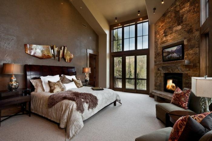 chambre à coucher adulte moderne en taupe et blanc, tapis gris, fauteuils couleur taupe, déco murale originale; mur en pierre authentique