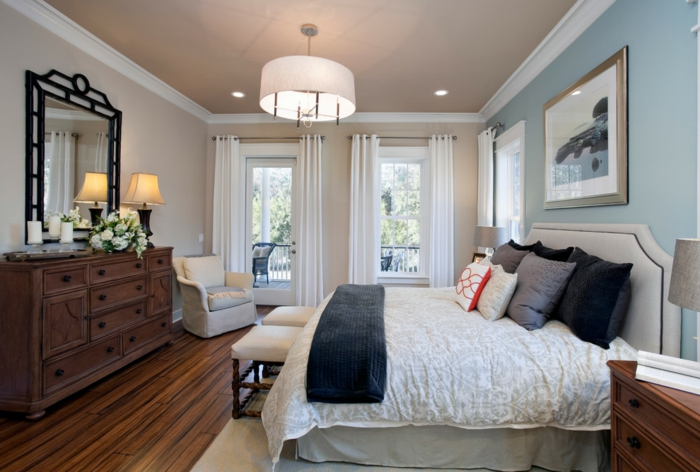 peinture chambre adulte 2 couleurs, sol en bois, tabourets beiges, miroir baroque, mur beige et mur bleu, grand buffet en bois et plafonnier rond, coussins déco gris