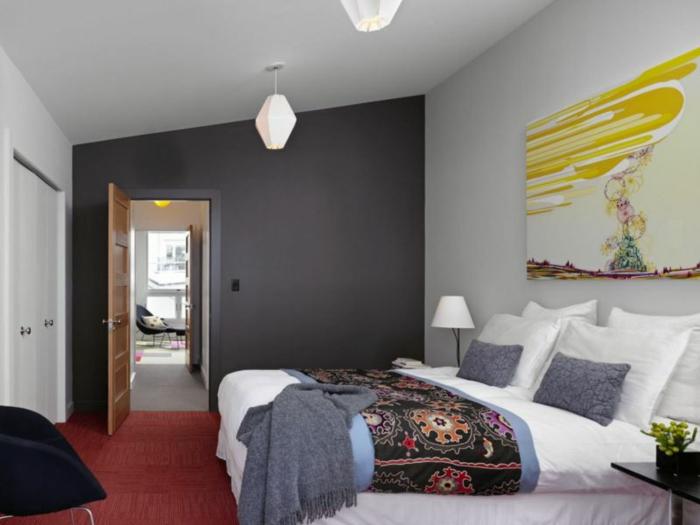 chambre monochrome, tapis rouge, chaise noire, mur gris anthracite, tableau peinture abstraite, plaid ethnique