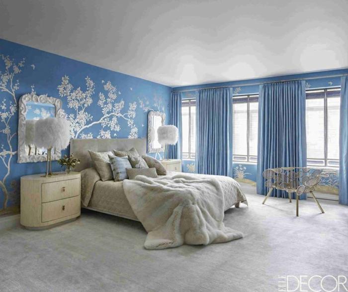 chambre adulte plongée dans le bleu et le blanc, petites commodes de chevet blanches, lampes à plumes, tapis gris, miroirs blancs