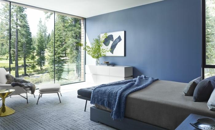 intérieur ouvert à l'extérieur avec un mur vitré, lit moderne gris, console moderne blanche, fauteuil blanc