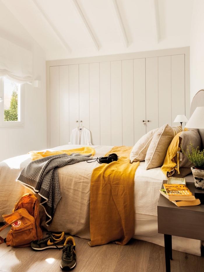la couleur jaune moutarde en forme accessoires plaid et coussins dans une chambre blanche avec parquet bois clair
