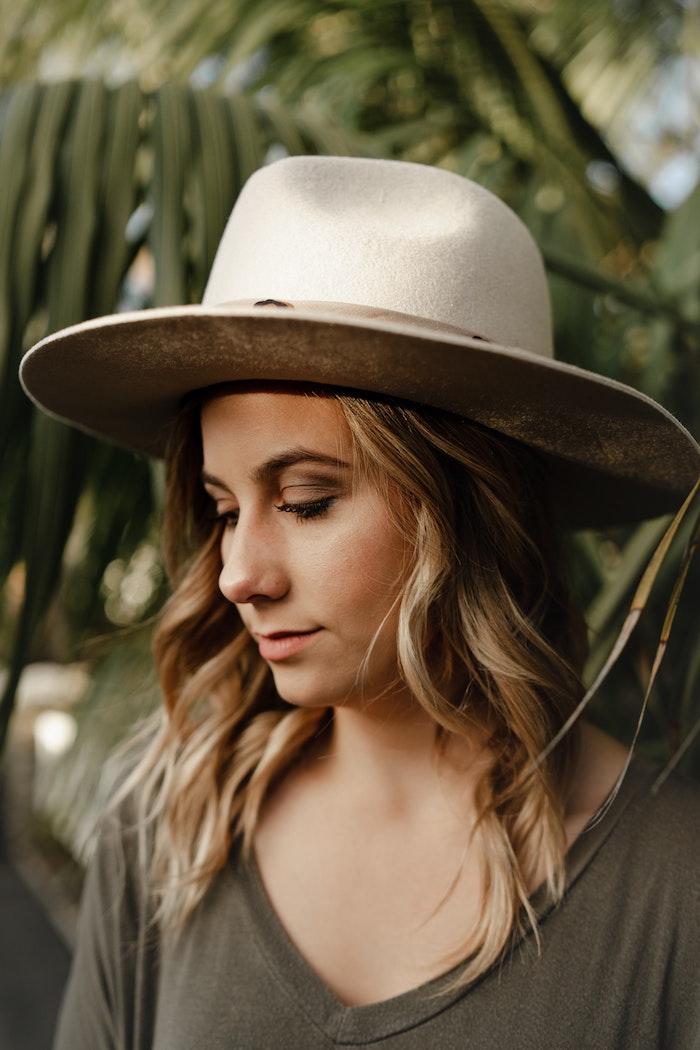 Belle femme avec chapeau dans la nature, plage avec palmes, coupe de cheveux mi long dégradé, belle femme idée portrait photo choix cheveux bouclés