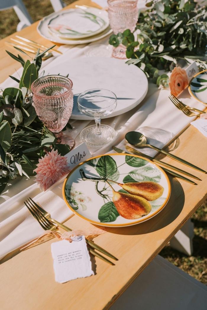 table en bois clair, assiettes aux poires, verres en cristal, branches d'olivier, ustensiles dorées