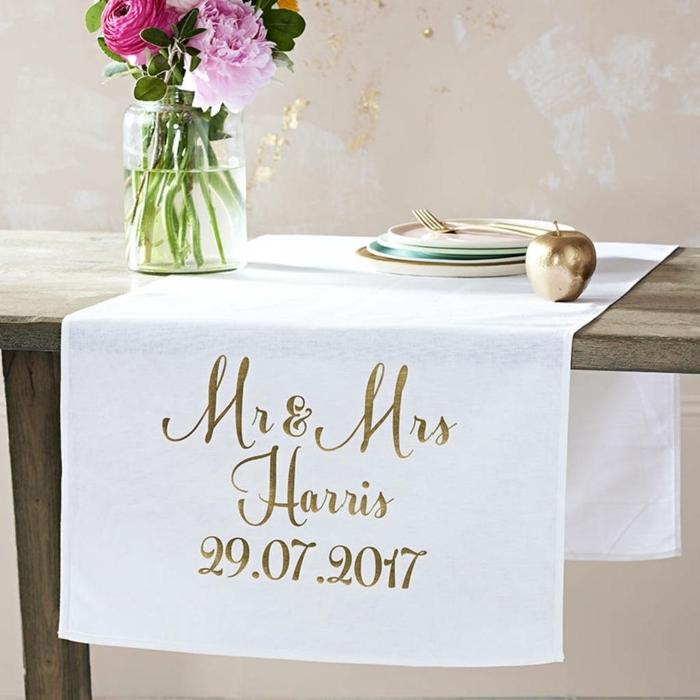 chemin de table blanc avec les initiales des mariés et la date, bocal en verre avec bouquet champêtre