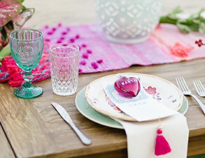 table en bois, sous assiette bleue, assiette blanche, verres en verre, chemin de table tissu, bougeoirs en verre, coeur rose, frange rose
