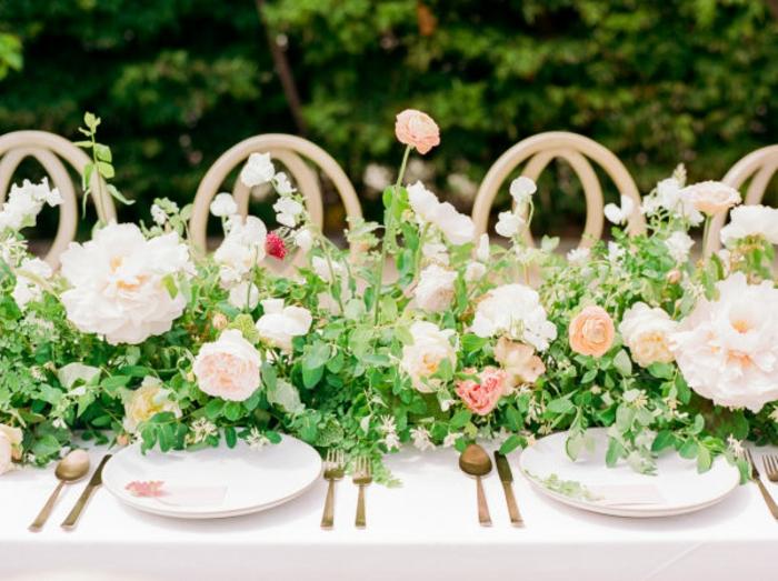 guirlande de fleurs comme chemin de table, chaises en bois aux dossiers originaux, ustensiles dorées, assiettes