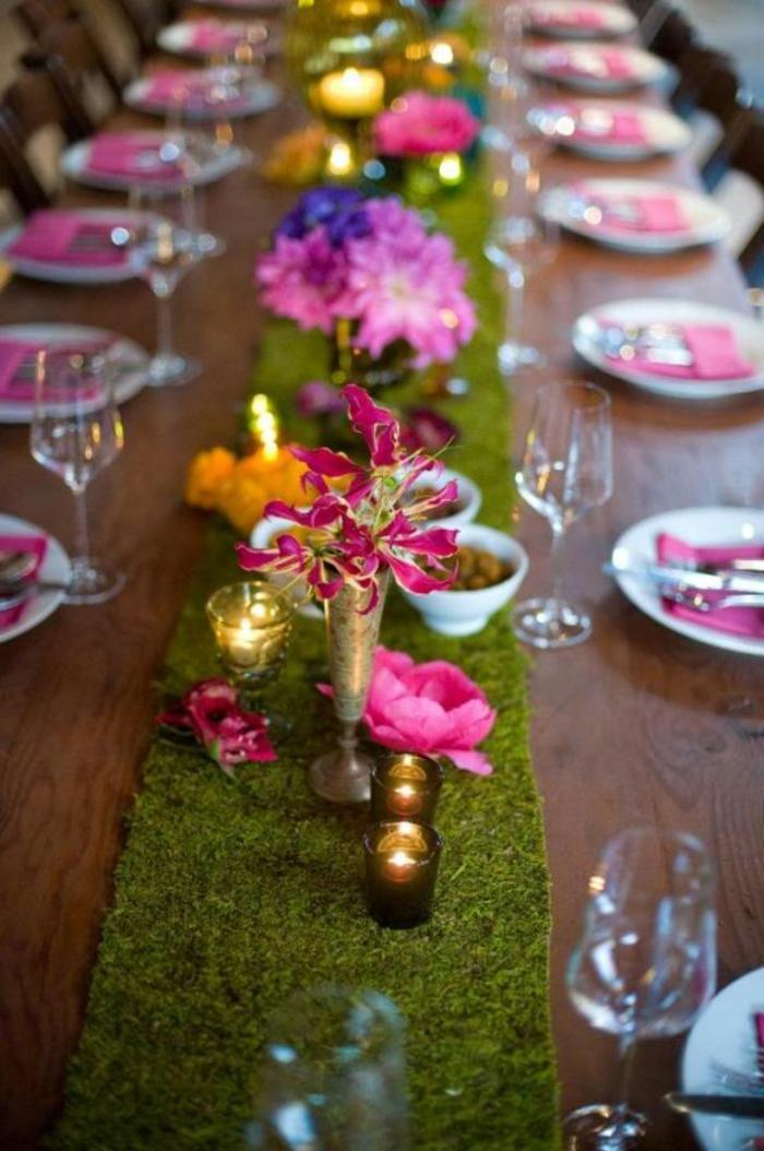 bande de mousse comme chemin de table, assiettes blanches, serviettes roses, porte-bougies