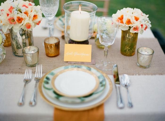 comment décorer la table de mariage, assiettes superposées, petits bouquets de jonquilles, chemin de table tissu, bougeoirs dorés