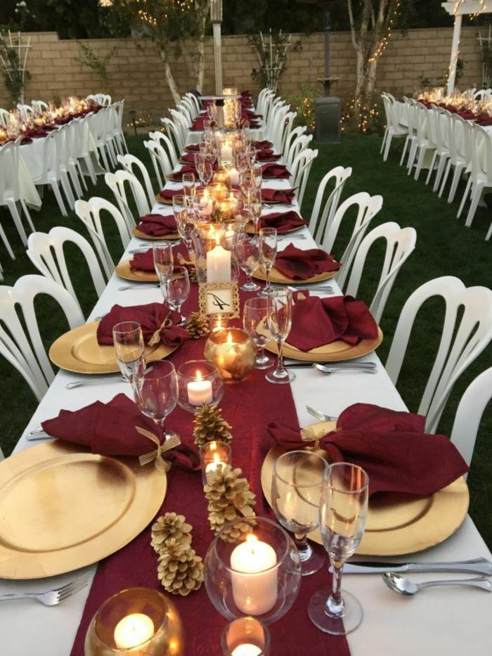 mariage à l'extérieur, chemin de table rouge, assiettes dorées plates, pommes de pin, serviettes rouges, nappe blanche