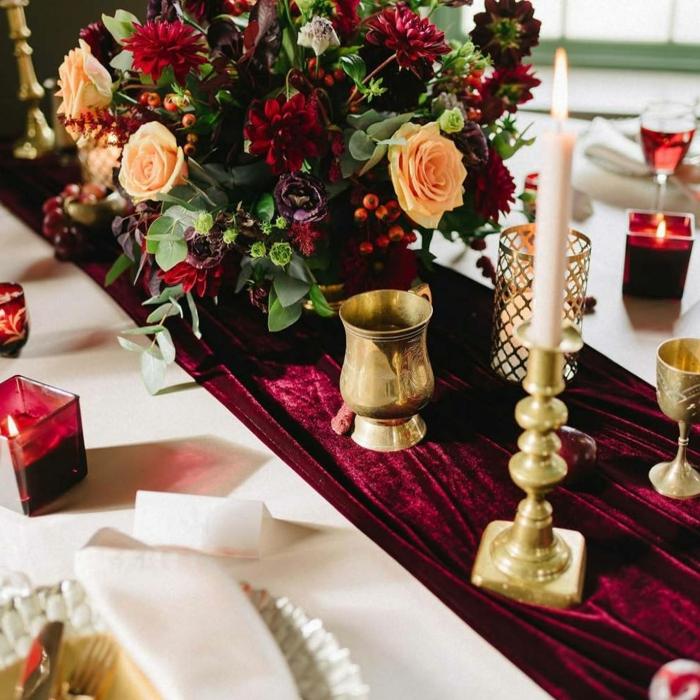 chemin de table rouge en velours, grand bouquet de roses et dahlias, porte bougie dorée et bougies rouges, table blanche