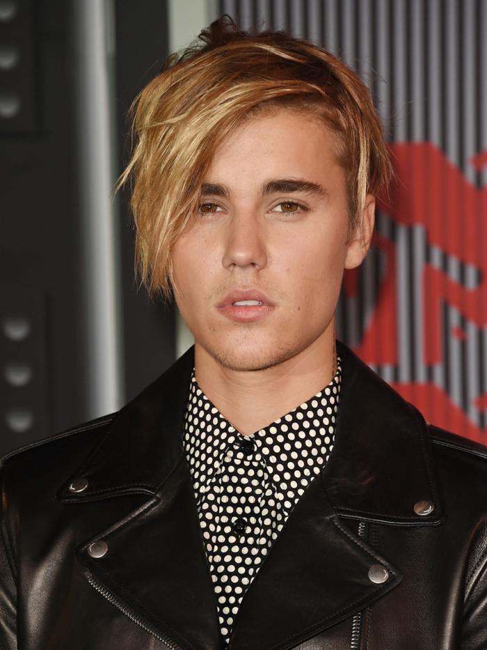 Justin Bieber avec un coupe moderne, cheveux blonds, frange sur le côté, chemise pointillé, veste noire