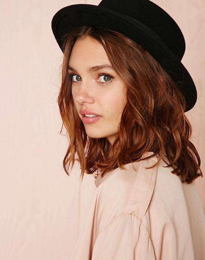 idée de coiffure boheme chic avec des boucles et raie au milieu, chapeau melon sur cheveux, chemise couleur crème