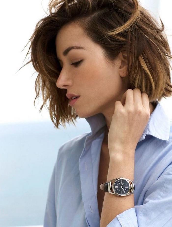 Belle femme avec montre luxueuse, cheveux mi-longs ondulés, chemise bleue, coupe cheveux mi long dégradé effilé avec frange, inspiration coupe femme