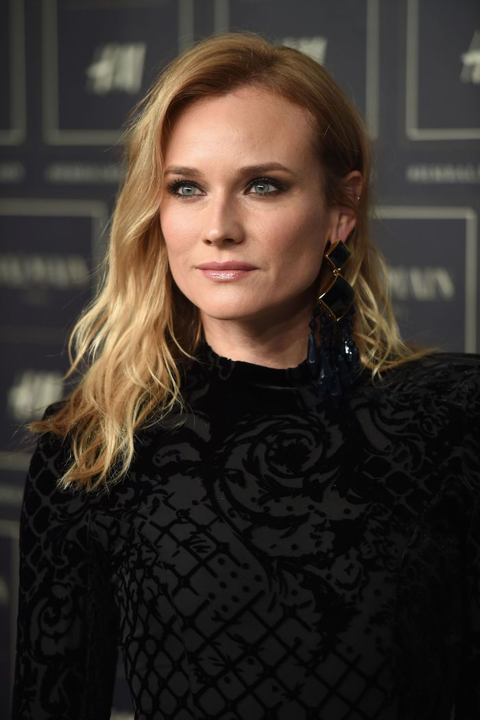 Diane Kruger look moderne chic, robe noire, boucles d'oreille, blonde femme maquillage, coupe mi courte femme, coiffure coiffée décoiffée photo idée