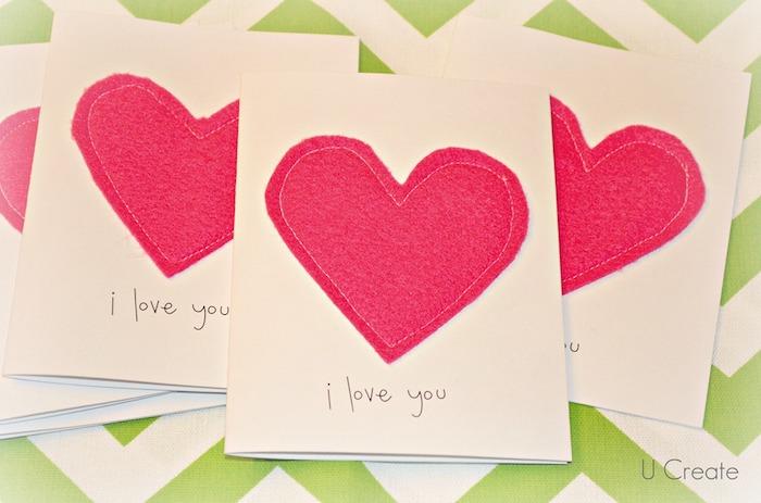 coeur rouge en feutrine collé sur papier blanc avec un message simple je t aime, activité manuelle maternelle saint valentin