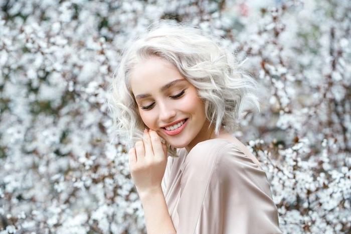 coloration blond polaire sur cheveux ondulés, blouse femme beige, idée de coiffure à effet décoiffé, maquillage nude