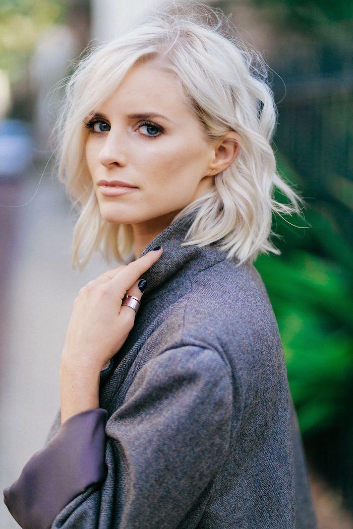 coloration blond polaire sur cheveux ondulés avec aspect décoiffé, mèche couvrant une partie du front, manteau gris
