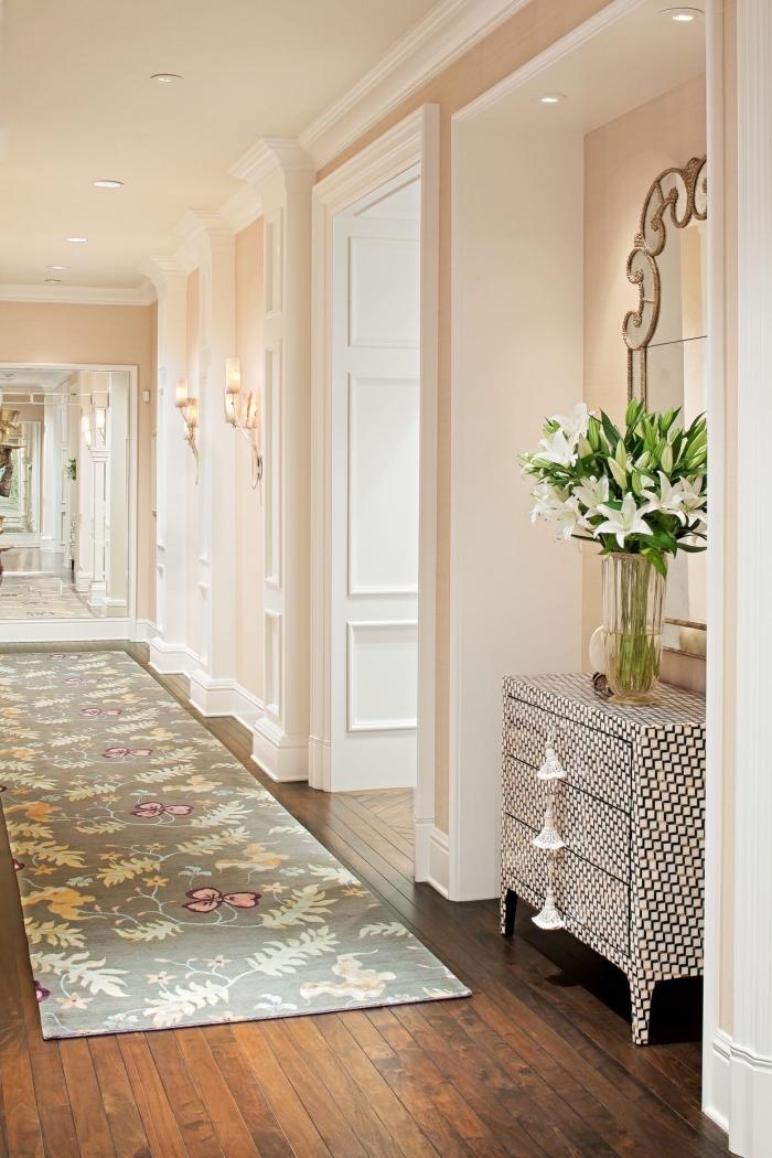 idée de couleurs pour peindre un couloir avec beaucoup de portes, couloir long et étroit illuminé par une peinture couleur pêche très claire combinée avec du blanc, déco douce et féminine avec un tapis de couloir vert amande à motifs végétaux qui reprend les couleurs des murs