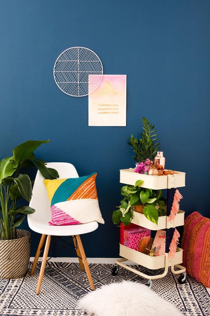 coin d'un salon bleu aménagé dans un style bohème chic avec un tapis ethnique graphique, des plantes verte et une desserte raskog ikea qui joue le rôle d'une étagère mobile