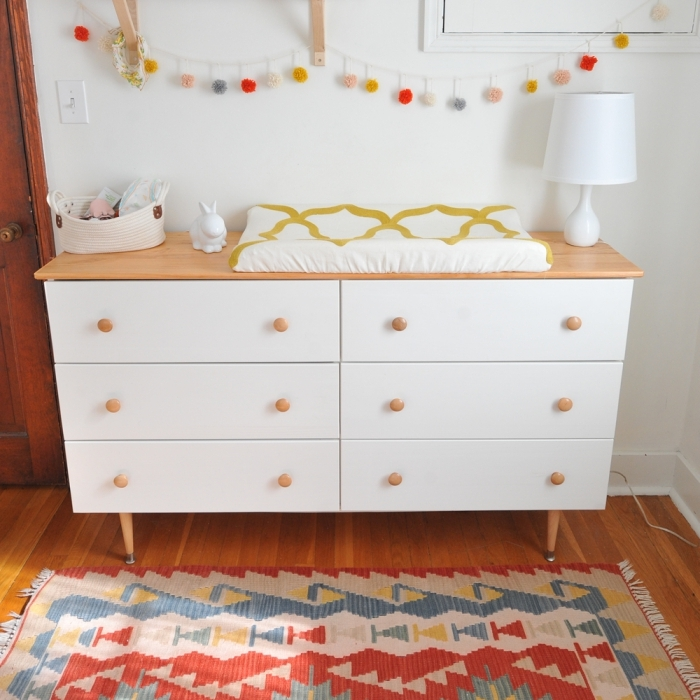une commode ikea tarva à façade repeinte en blanc avec des pieds en bois scandinave transformée en table à langer