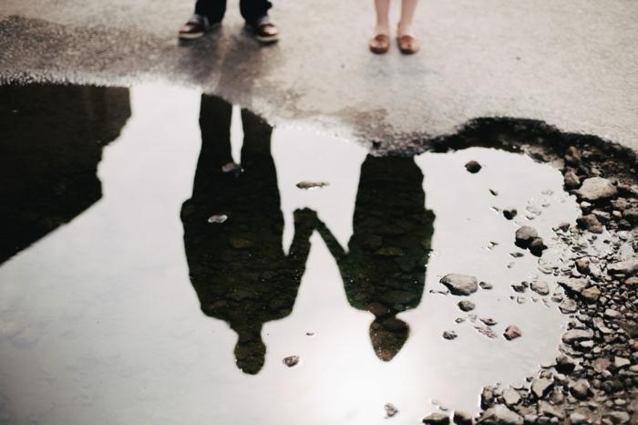 Coeur forme de trou sur le sol, silhouettes de couple amoureux qui se prennent la main, miroir vue sur l'eau