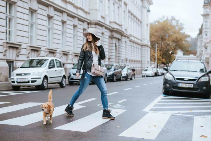 Femme avec sin chien sur un passage piéton, jean et veste cuir, voitures parqués sur la rue, marque vetement femme, look tumblr, photo tumblr fille moderne