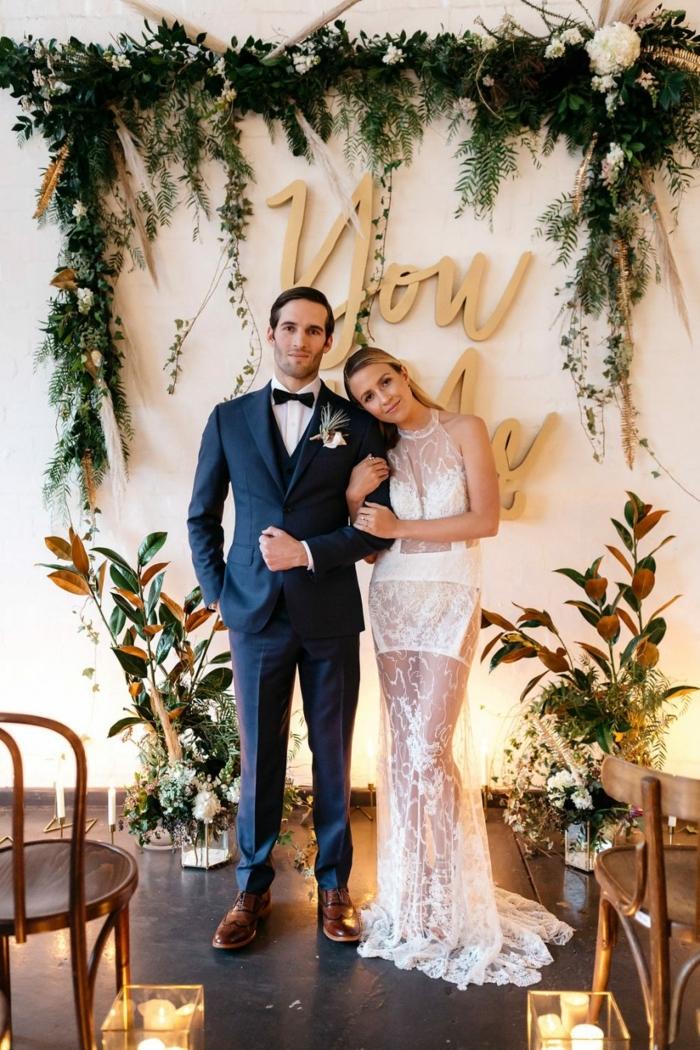 costume homme pour mariage bleu, robe blanche dentelle, parite transparente, déco murale guirlande de fleurs