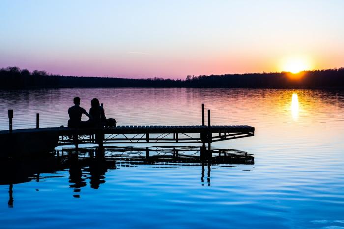 Au bord d'un lac au coucher du soleil, image romantique, couple romantique, jour festive en fevrier, silhouettes homme et femme image pour saint valentin